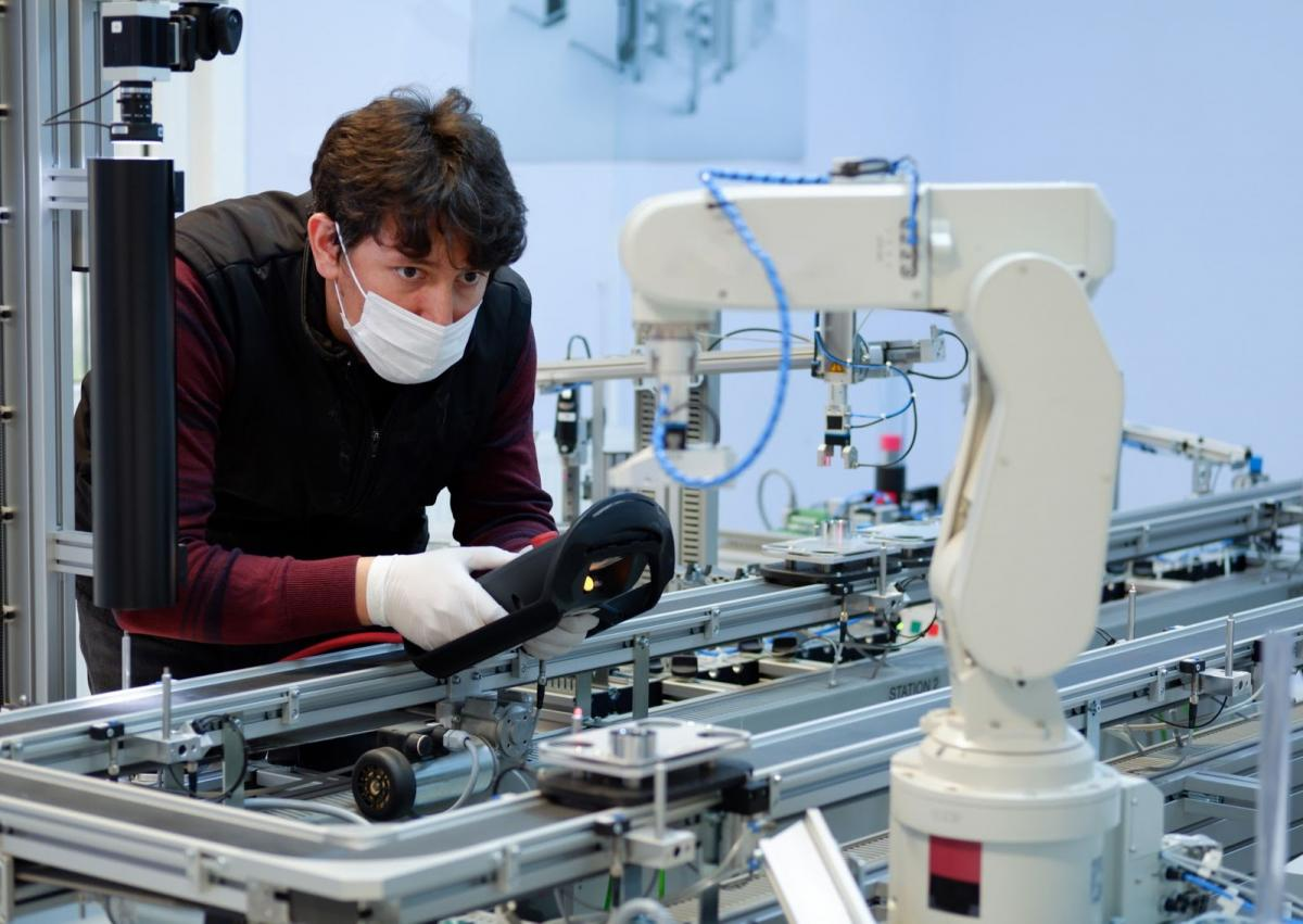Man looking closely to a robotic arm