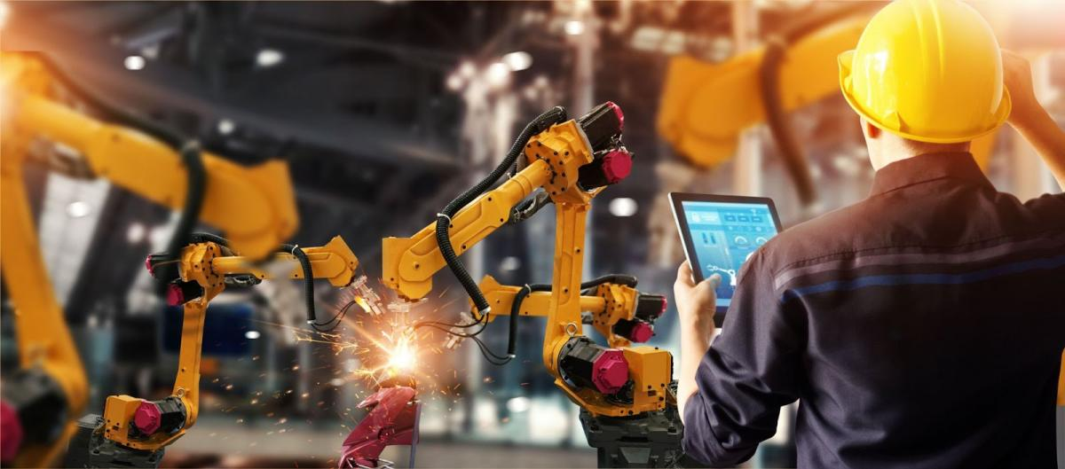 Man with tablet looking at robotic arms