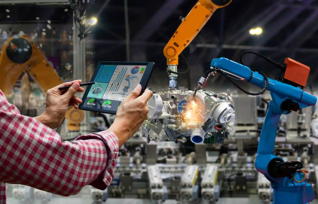 Engineer with touch screen in factory with industrial robots